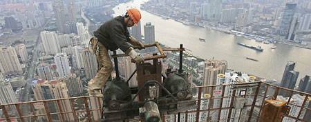 A man goes about his work on the construction site of the Shanghai World Financial Center on November 4, 2006 in Shanghai, China. (Photo by China Photos/Getty Images)