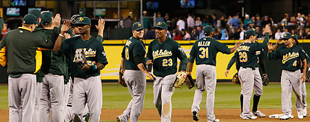 Oakland Athletics' players congratulate each other after a game. (AP Photo/Kevin P. Casey)