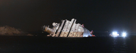 The luxury cruise ship Costa Concordia leans on its side after running aground the tiny Tuscan island of Giglio, Italy, Saturday, Jan. 14, 2012. (AP Photo/Gregorio Borgia)
