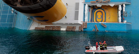 Italian scuba divers approach the cruise ship Costa Concordia leaning on its side, the day after running aground the tiny Tuscan island of Giglio, Italy, on Sunday, Jan. 15, 2012. (AP)