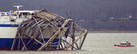 The Delta Mariner is idle at the US68/KY80 Eggner Ferry Bridge, with two destroyed spans of the bridge draped over her bow, on Kentucky Lake near Golden Pond, Ky., Friday, Jan. 27, 2012. (AP Photo/Stephen Lance Dennee)