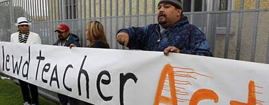 Edgar Flores, right, encourages other parents to join a protest outside Miramonte Elementary school in Los Angeles Monday, Feb. 6, 2012. (AP Photo/Damian Dovarganes)