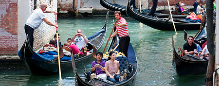 Gondoliers navigate through traffic as they transport tourists along a tightly packed canal near the Rialto bridge on August 11, 2011 in Venice, Italy.  (Photo by Marco Secchi/Getty Images)