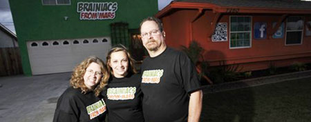Sarah Hostetler (center) and her parents Beth and Scott pose in front of their home (Josh Edelson/Reuters)