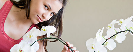 Young woman smelling orchids (Corbis)