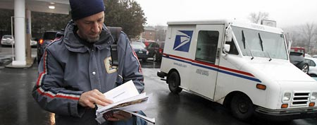 File: Mail carrier Mike Gillis delivers mail. (AP Photo/Toby Talbot)