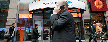 People walking by AT&T store. (AP Photo/Mark Lennihan)