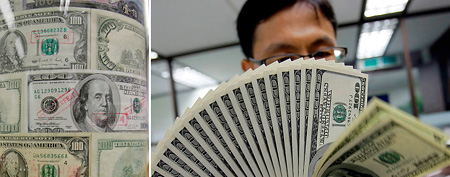 A South Korean bank clerk stands next to a show case of counterfeit U.S. dollar bills at a local bank in Seoul, South Korea, Thursday, June, 11, 2009. (AP Photo/Lee Jin-man)