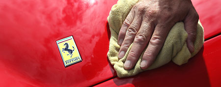 A man polishes the bonnet of a Ferrari sports car.  (Photo by Dan Kitwood/Getty Images)