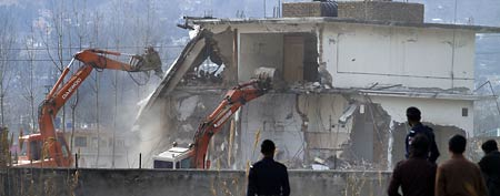 Pakistani police officers stand guard as authorities use heavy machinery to demolish the compound of Osama bin Laden in Abbottabad, Pakistan on Sunday, Feb. 26, 2012. (AP Photo/Anjum Naveed)