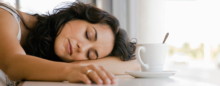Tired woman at a cafe. (Thinkstock)