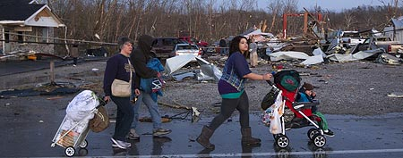 A family walks by damaged buildings that lay in ruin after a tornado touched near Henryville, Ind., Friday March 2, 2012. (AP Photo/Philip Scott Andrews)