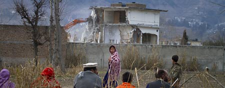 A Pakistani family watches the destruction of Osama bin Laden's compound in Abbottabad, Pakistan. Feb. 26, 2012. (AP Photo/Anjum Naveed, File)