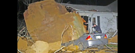 Boulder sits on top of smashed car. (Yahoo! video)