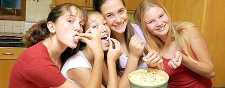Girls eating popcorn. (ThinkStock)
