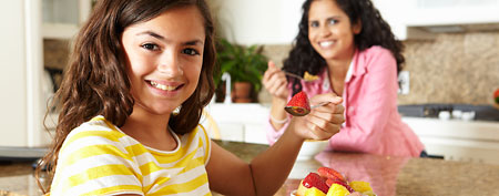 Mother and daughter eating fruit (Thinkstock)