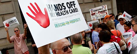 A sign is held during a protest against President Barack Obama's health care reform plan outside the 11th Circuit Court of Appeals in Atlanta, Wednesday, June 8, 2011. (AP Photo)