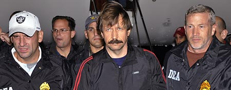 Russian arms trafficking suspect Viktor Bout, center, is led by DEA officers off a flight From Bangkok to New York. (AP Photo)