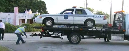 A Miami Police Department patrol cruiser rests on a wrecker flat bed after being rescued from a precarious position.