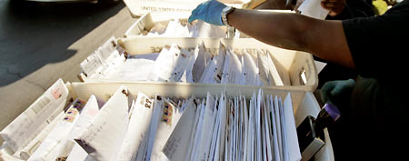 Mail handler Romon Finklea sorts envelopes containing income tax forms at a mail drop at the North Little Rock, Ark., U.S. Postal service center on Tuesday, April 15, 2008. (AP Photo/Danny Johnston)