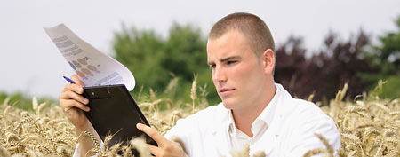 Young man looking at paperwork in a field (Thinkstock)