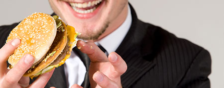 Businessman eating a hamburger (Thinkstock)