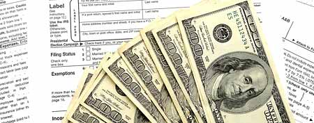 Cash with tax forms (Thinkstock)