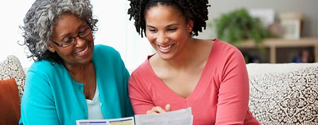 Adult daughter helping mother with paperwork (Corbis)