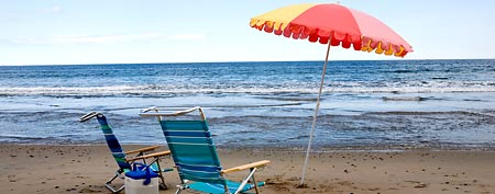 Chairs and umbrella on a beach (Thinkstock)