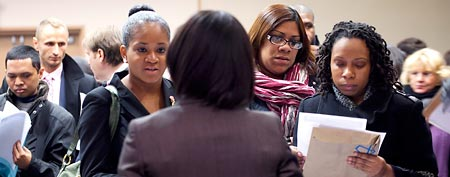 In this Dec. 12, 2011 photo, people talk with a recruiter, center, at a job fair sponsored by National Career Fairs, in New York. (AP Photo/Mark Lennihan)
