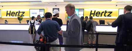 Customers wait in line at a Hertz rental car counter at San Jose International Airport in San Jose, Calif., Monday, May 9, 2011. (AP Photo/Paul Sakuma)