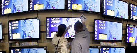 In this Nov. 25, 2011 file photo, shoppers look at televisions displayed at a Best Buy store, in Brentwood, Tenn. (AP Photo/Mark Humphrey, File)