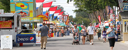 The cheapest cities in America. In this photo: Fair goers walk the grounds on the opening day of the Colorado State Fair in Pueblo, Colo. (AP)