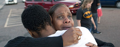 "Shamecca Davis hugs her son Isaiah Bow, who was an eye witness to the shooting, outside Gateway High School where witness were brought for questioning. After leaving the theater Bow went back in to find his girlfriend. "" I didn't want to leave her in there. But she's ok now,"" Bow said. (AP Photo/Barry Gutierrez)"