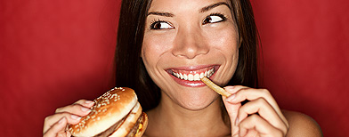 Girl eating holding a burger and fries (Fotolia stock image)