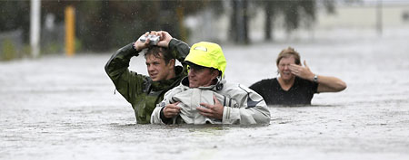 Chuck Cropp, center, his son Piers, left, and wife Liz, right, wade through floodwaters from Hurricane Isaac Wednesday, Aug. 29, 2012, in New Orleans. (AP Photo/David J. Phillip)