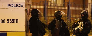 Armed police officers patrol in North Belfast (PA)