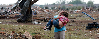 A woman carries a child in the aftermath of a tornado (PA)