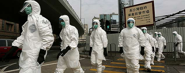 Health workers in full protective gear walk at a wholesale poultry market (PA)