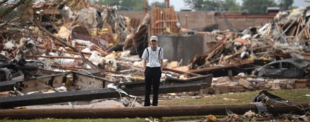 A man stands among the wreckage after a tornado struck Moore, Oklahoma, May 20, 2013. (REUTERS/Gene Blevins)