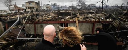 Robert Connolly and his wife, Laura, survey the remains of the home owned by her parents that burned to the ground in the Breezy Point section of New York. (Mark Lennihan/AP)