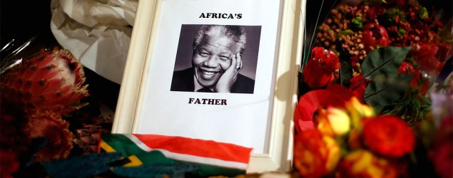 Flowers and tributes are left on the Nelson Mandela statue in Parliament Square in London. (Reuters)