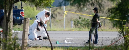 Forensic technicians work at a crime scene in the municipality of Cadereyta May 13, 2012. (REUTERS/Josue Gonzalez)