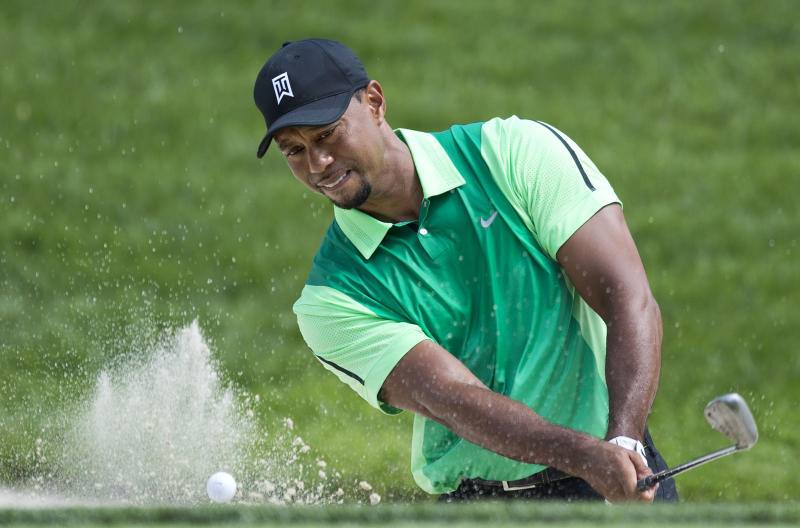 US golfer Tiger Woods swings from a bunker during the first round of the Quicken Loans National at Congressional Country Club in Bethesda, Maryland, June 26, 2014