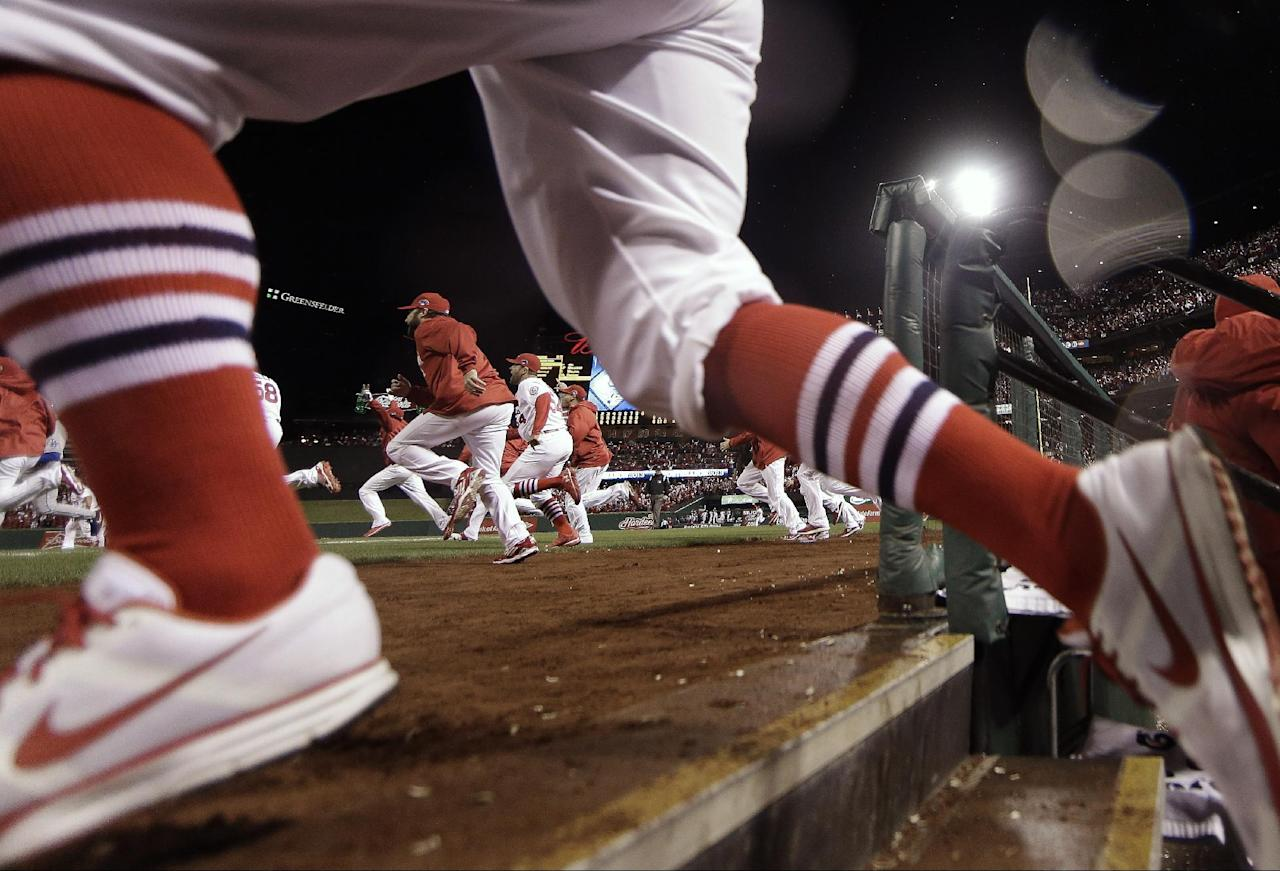 The St. Louis Cardinals run out of the dugout after Game 6 of the National League baseball championship series against the Los Angeles Dodgers, Friday, Oct. 18, 2013, in St. Louis. The Cardinals won 9-0 to win the series. (AP Photo/Jeff Roberson)