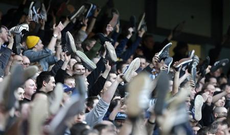 Leeds United supporters wave their shoes in the air as they sing during their FA Cup fifth round soccer match against Manchester City at The Etihad Stadium in Manchester