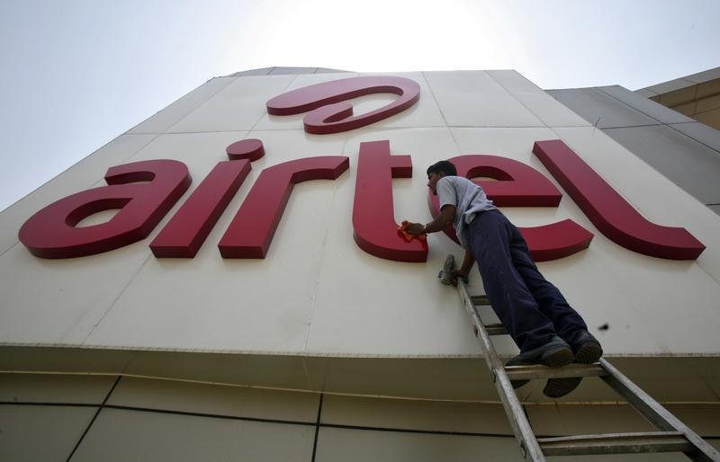 A worker cleans a logo of Bharti Airtel at its zonal office building in the northern Indian city of Chandigarh