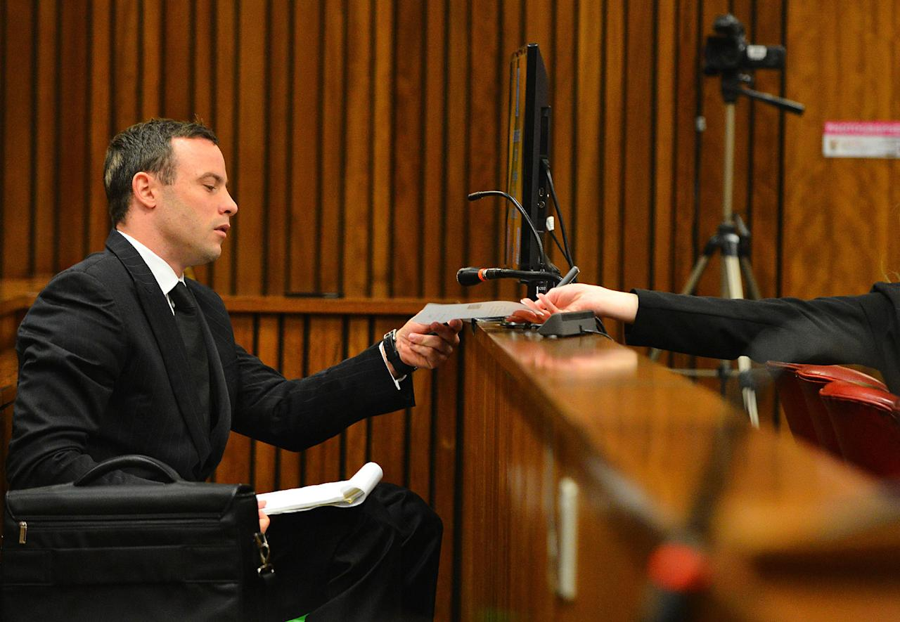 Oscar Pistorius passes a note to his defense team in court in Pretoria, South Africa, Monday June 30, 2014. The trial resumed Monday, after one month during which mental health experts evaluated the athlete to determine if he has an anxiety disorder that could have influenced his actions on the night he killed girlfriend Reeva Steenkamp. (AP Photo/Phill Magakoe, Pool)