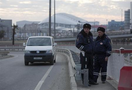 Russian traffic police officers stand guard during patrol on a road near venues at the Olympic Park near Sochi