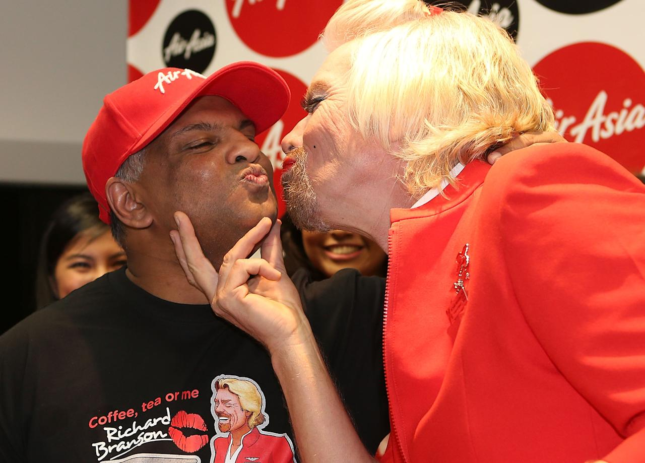 PERTH, AUSTRALIA - MAY 12:  Sir Richard Branson gives Tony Fernandes a kiss before boarding his flight to Kuala Lumpur at Perth International Airport on May 12, 2013 in Perth, Australia. Sir Richard Branson lost a friendly bet to AirAsia Group Chief Executive Officer Tony Fernandez after wagering on which of their Formula One racing teams would finish ahead of each other in their debut season of the 2010 Formula One Grand Prix in Abu Dhabi and that the loser would serve as a female flight attendant on board the winner's airline.  (Photo by Paul Kane/Getty Images)